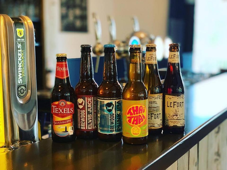 Verschillende flesjes bier met staan op de bar in Grotel's Genieten.